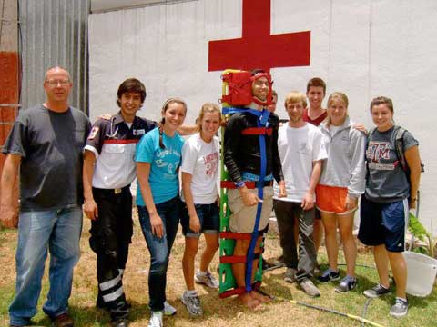CIAO students in front of a wall with a red cross on it
