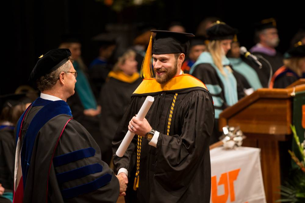 Student accepting diploma from Dean Alway
