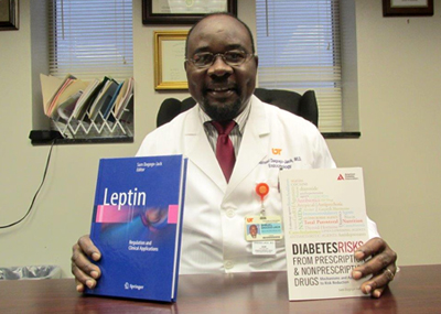 Dr. Dagogo-Jack sitting at a desk holding two of his recently published books