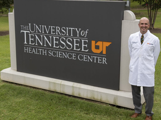 Program Director in front of UTHSC sign