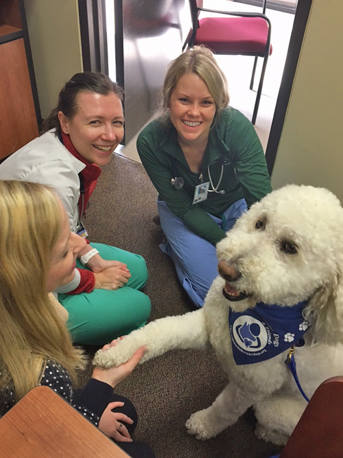 Three female residents with a white therapy dog