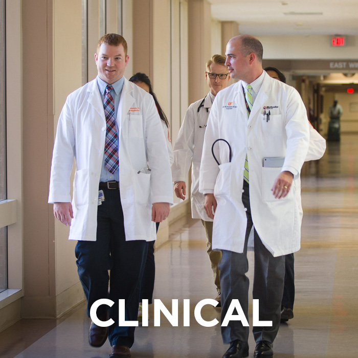 "Resident walk down the hall of hospital with attending doctor. The word ""clinical"" is imposed on top of the photo."