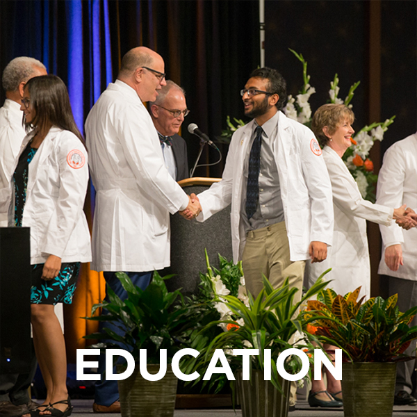 "Male student shaking the dean's hand at white coat ceremony. The word ""education"" is imposed on the lower part of the image."