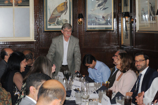 Dr. Wall addressing laughing faculty, fellows, and guests at the table
