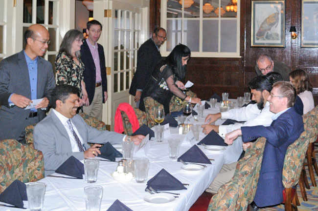 Faculty, fellows, and guests talking at a table