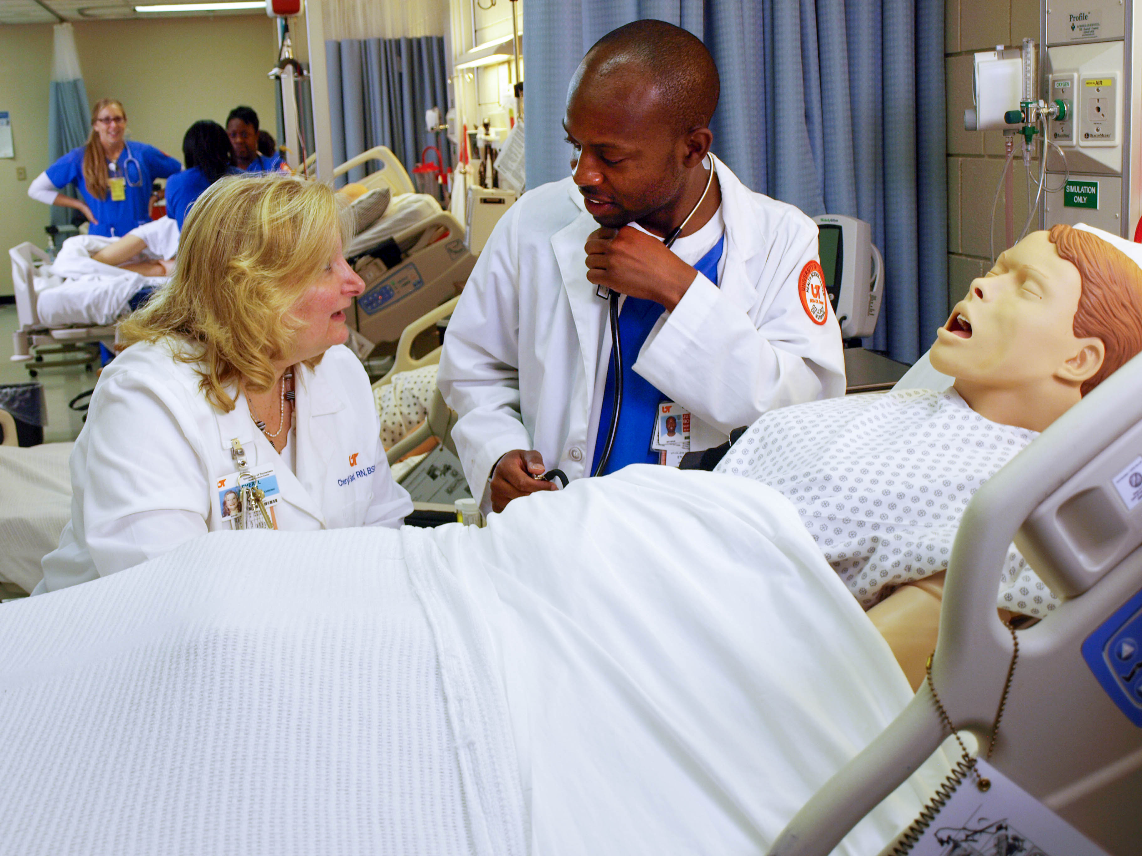 Nursing student receives instruction in simulation lab.