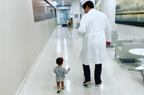 TDoctor and toddler walking down a hospital hallway