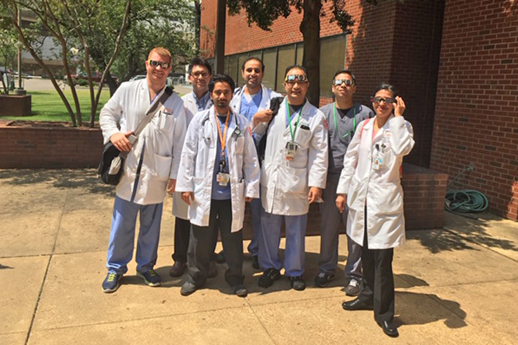 Fellows ouside in white coats and sunglasses